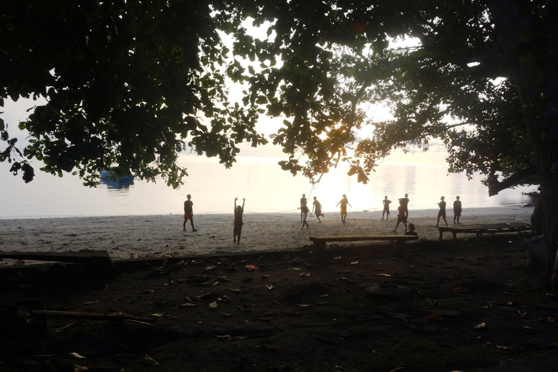 Kids playing soccer at the beach
